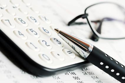 Lunettes, stylo et calculatrice illustrant l'importance du travail dans la genèse de la myopie.
